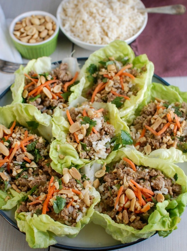 Thai Turkey Brown Rice Lettuce Wraps mix your favorite Asian flavors into a crisp, healthy lettuce wrap. Ground turkey is simmered in lime juice, ginger, soy sauce and red chili garlic sauce and mixed with brown rice. Top these with fresh cilantro, matchstick carrots and crunchy peanuts and you have a healthy meal.
