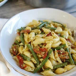 Pesto Pasta with Green Beans, Sun-dried Tomatoes and Toasted Pine Nuts in a bowl
