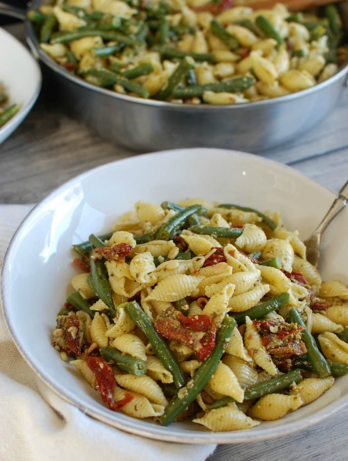 Pesto Pasta with Green Beans Sun-dried Tomatoes and Toasted Pine Nuts with spoon.
