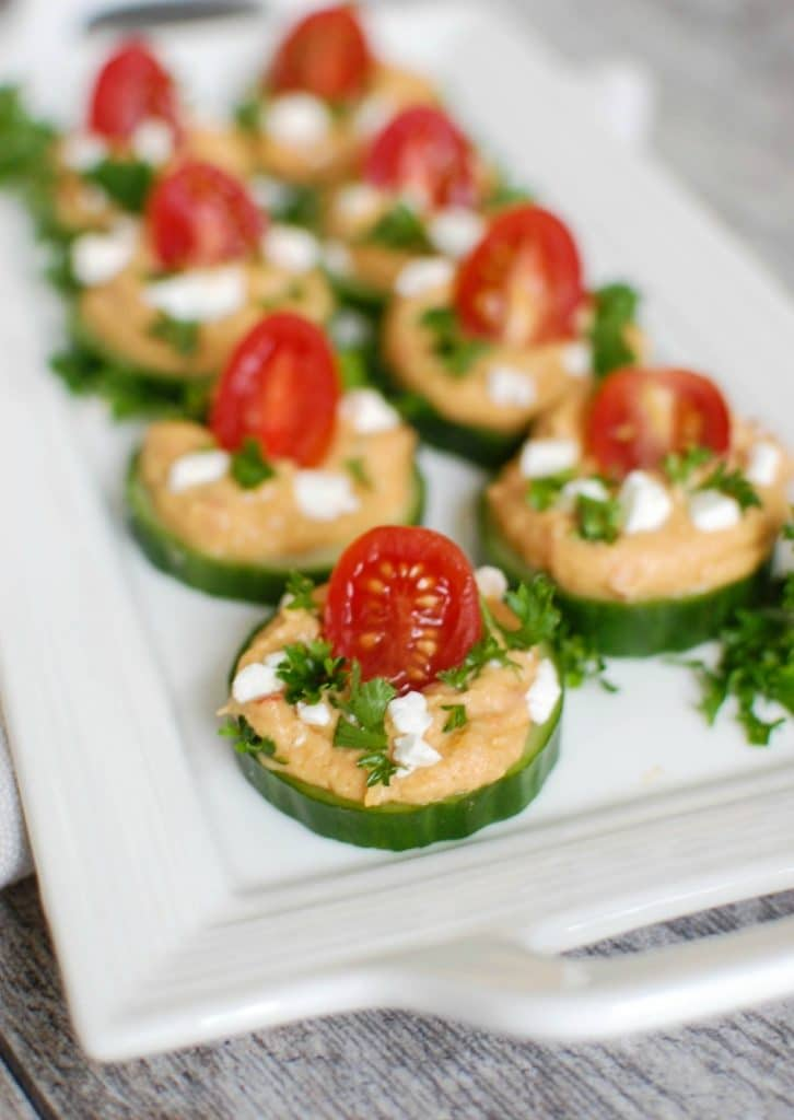 Cucumber Hummus Bites make the perfect finger food and appetizer for your next party or get together. Crisp cucumbers slices are topped with roasted red pepper hummus, tomatoes, feta cheese and fresh parsley.