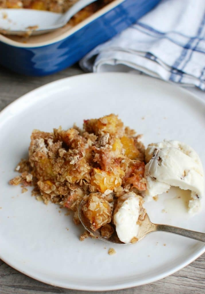 Peach Crisp is the best summer dessert. Fresh, warm peaches are topped with a crumbly topping and paired with ice cream.