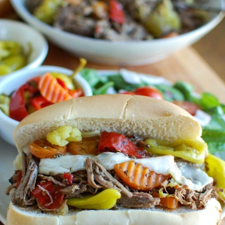 Slow Cooker Italian Beef Sandwiches make a great game day food or weeknight dinner that easily cooks in your crockpot. Chuck roast is slowly cooked in Italian seasonings, beef broth and mixed with pepperoncini peppers and Giardiniera. Toast the beef in a hoagie bun with provolone cheese and extra pepperoncini and Giardiniera for the perfect sandwich.