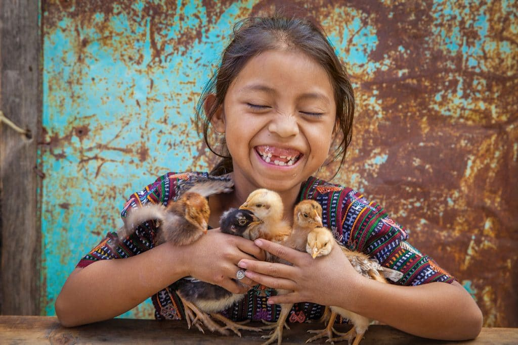 Yennifer holds baby chicks her family received as a part of the Gift Catalog program.