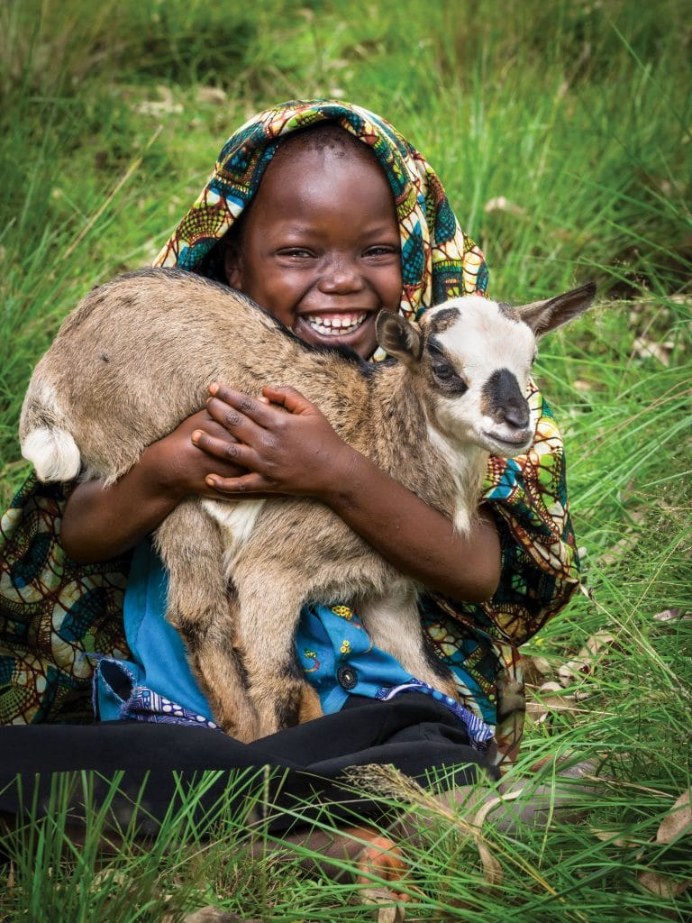 "Gasorwe, Burundi. Gift Catalog: Chanian Niyonyishu, girl child, 5-years-old, pictured with a baby goat. Quote from mother, Zuena Mukeshimana: ""With the goat we received, we can now fertilize our ground for better food production."""