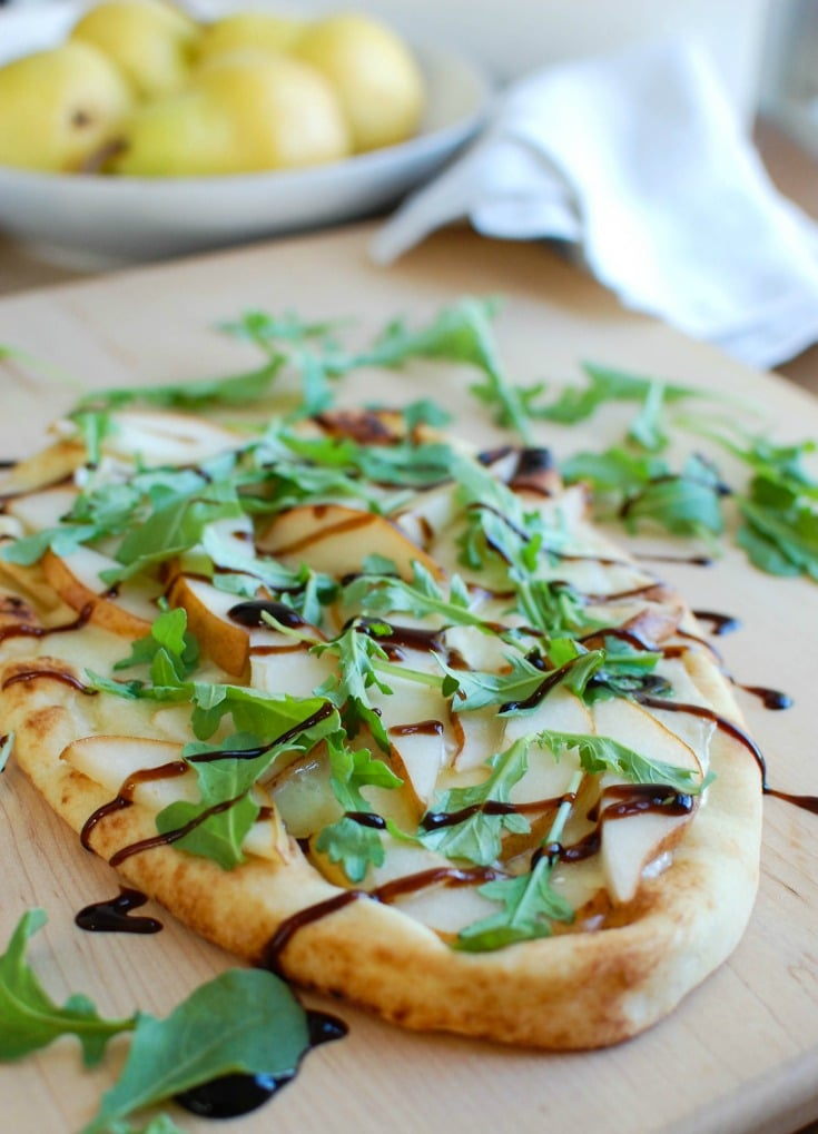 Warm Pear Brie Arugula Naan is the perfect holiday appetizer that will impress your guests. This beautiful flatbread is warmed in the oven with brie cheese and pear and then topped with arugula and a drizzle of balsamic glaze.