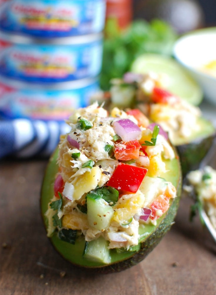Tropical Tuna Stuffed Avocado is the perfect, quick and healthy lunch at your desk or on-the-go. Fresh mango, cilantro, fresh vegetables and lime juice is mixed with Sold White Albacore Tuna and Greek Yogurt and then stuffed in a delicious avocado.