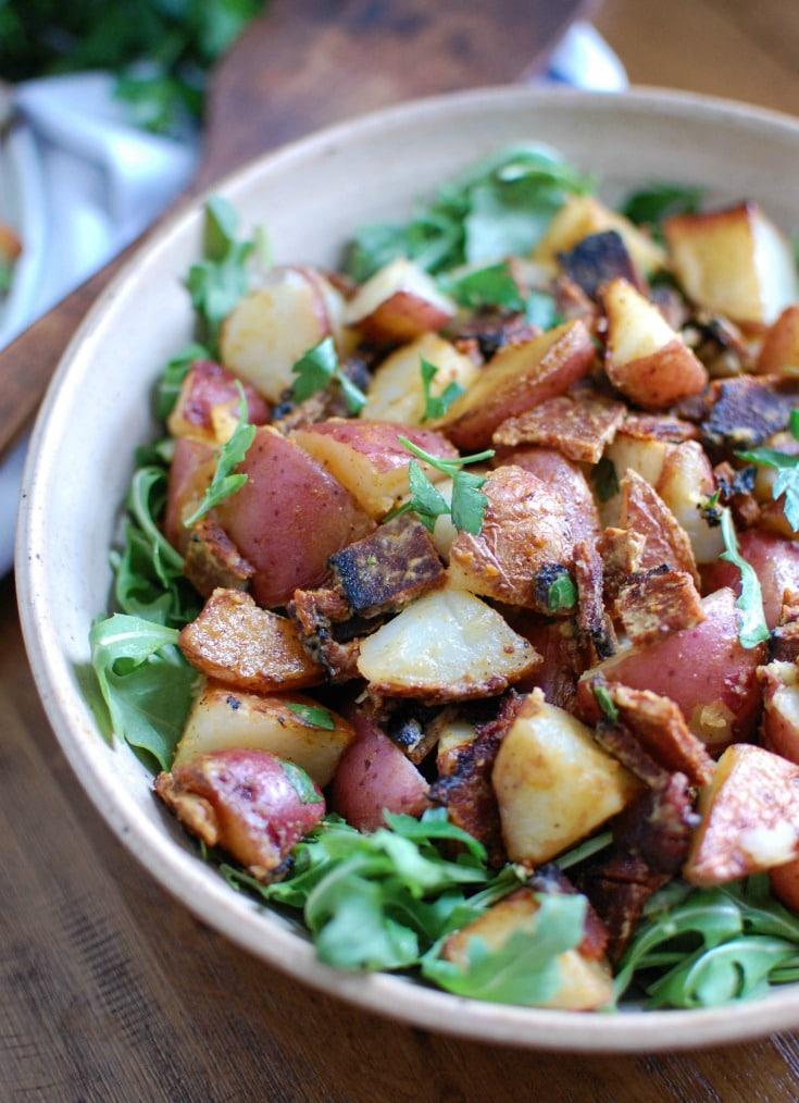 Warm, crispy potatoes are paired with crispy bacon, peppery arugula and is tossed in a mustard dressing in this Warm Potato Bacon Salad. This makes a hearty side dish or salad paired with your favorite meal.