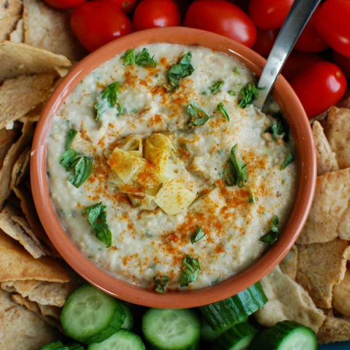 White Bean Artichoke Dip is a healthy appetizer, snack or spread for sandwiches. White beans, artichokes, lemon juice, olive oil, cayenne pepper, basil and garlic are blended and topped with fresh basil and parsley to create a healthy, flavorful dip.