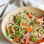 Asian Cucumber Noodle Salad is a light and healthy salad or side dish. Cucumber and red onion noodles, carrots and jalapeños are tossed with a light Asian dressing.
