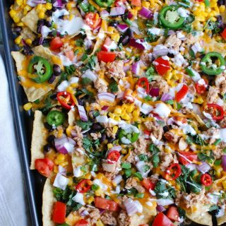 Southwestern Salmon Nachos take traditional nachos to a new level mixing salsa and salmon together and topping that with black beans, corn, shredded cheese, tomatoes, red onion, cilantro, green onion, jalapeños, red chiles and a drizzle of sour cream. These nachos are backed to perfection and are a nice lunch for Father's Day or football season.