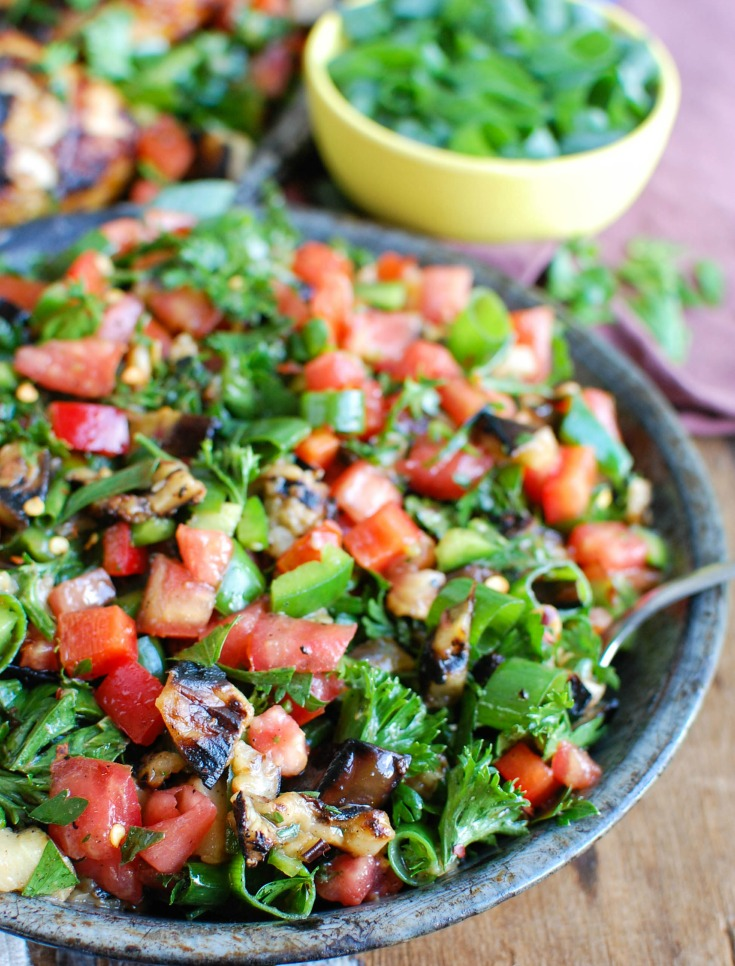 Mediterranean Eggplant Salad mixes grilled eggplant with fresh tomatoes, mint, parsley, green onion, bell pepper and tossed with olive oil, lemon juice, za'atar and crushed red pepper. This is the perfect side salad for a summer BBQ or party or to pair with grilled chicken or fish.