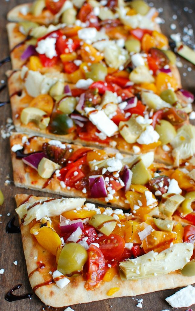 Mediterranean Flatbread is a quick and easy vegetarian meal made on your favorite flatbread or naan. Your favorite Mediterranean flavors of hummus, olives, artichokes, roasted peppers, feta cheese, tomatoes, red onion and balsamic glaze create a colorful, flavor packed appetizer or meal.
