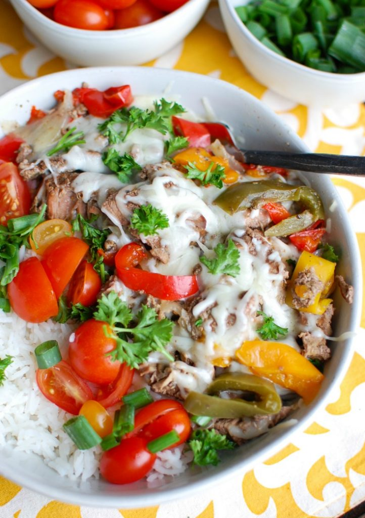 If you like philly cheesesteaks you will love this lighter take created with your slow cooker. Slow Cooker Philly Cheesesteak Rice Bowls features slow cooker beef cooked in a delicious marinade placed on top of a bed of rice with melted provolone cheese and your favorite toppings.