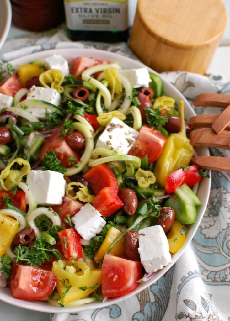 Spiralized Greek Style Salad with wooden tongs