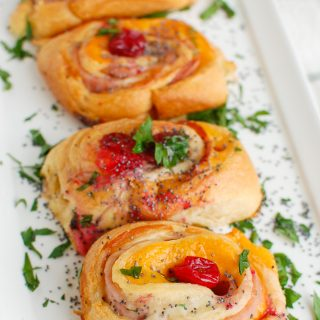 Ham Cheese and Cranberry Rollups on white platter