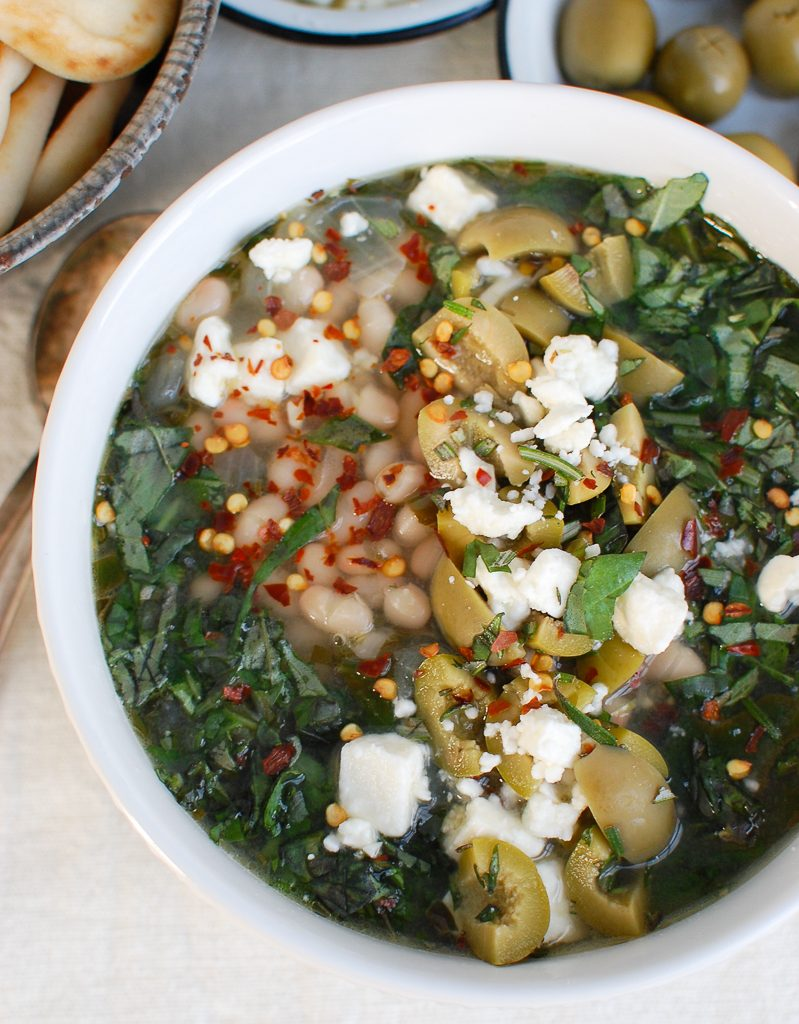 Navy Bean and Greens Soup with Feta and Olives in Big White Bowl