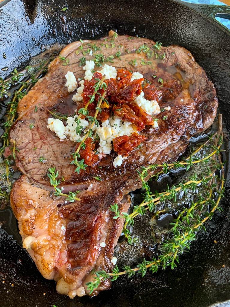 Pan-Seared Ribeye with Goat Cheese and Sun-dried Tomatoes in Skillet