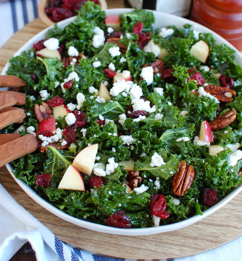 Kale Salad with Cranberries on a Wood Plate