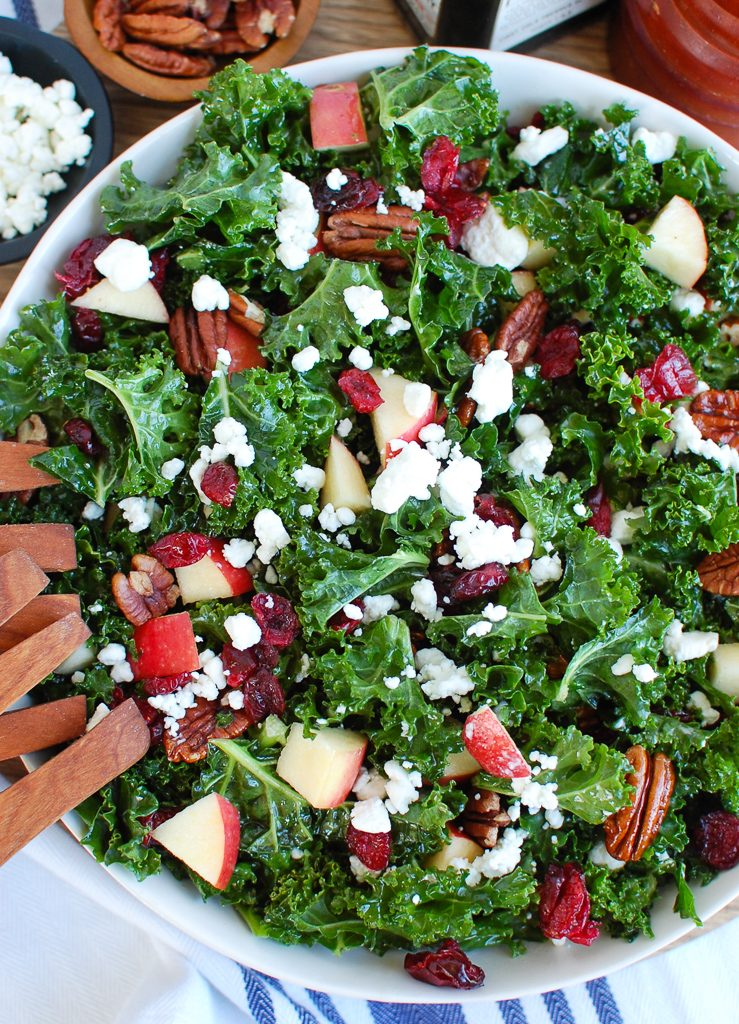 Kale Salad with Cranberries with Wooden Tongs