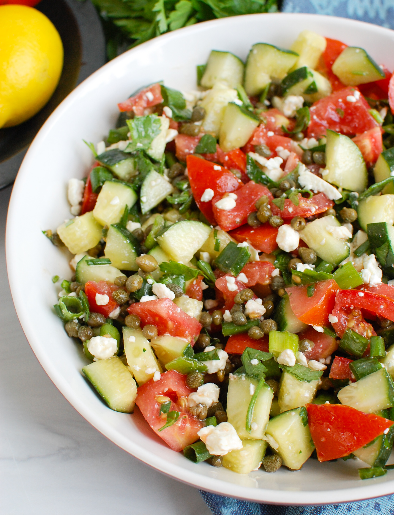 Tomato and Cucumber Salad with Capers in white bowl