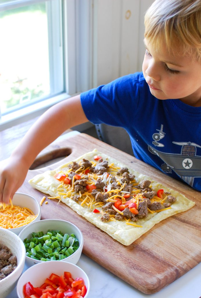 Turkey Sausage and Egg Puff Pastry Pizza with kid helping
