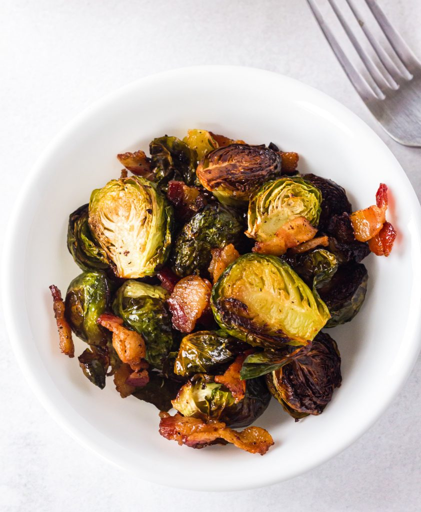 Roasted Brussels Sprouts with Bacon in white bowl with fork