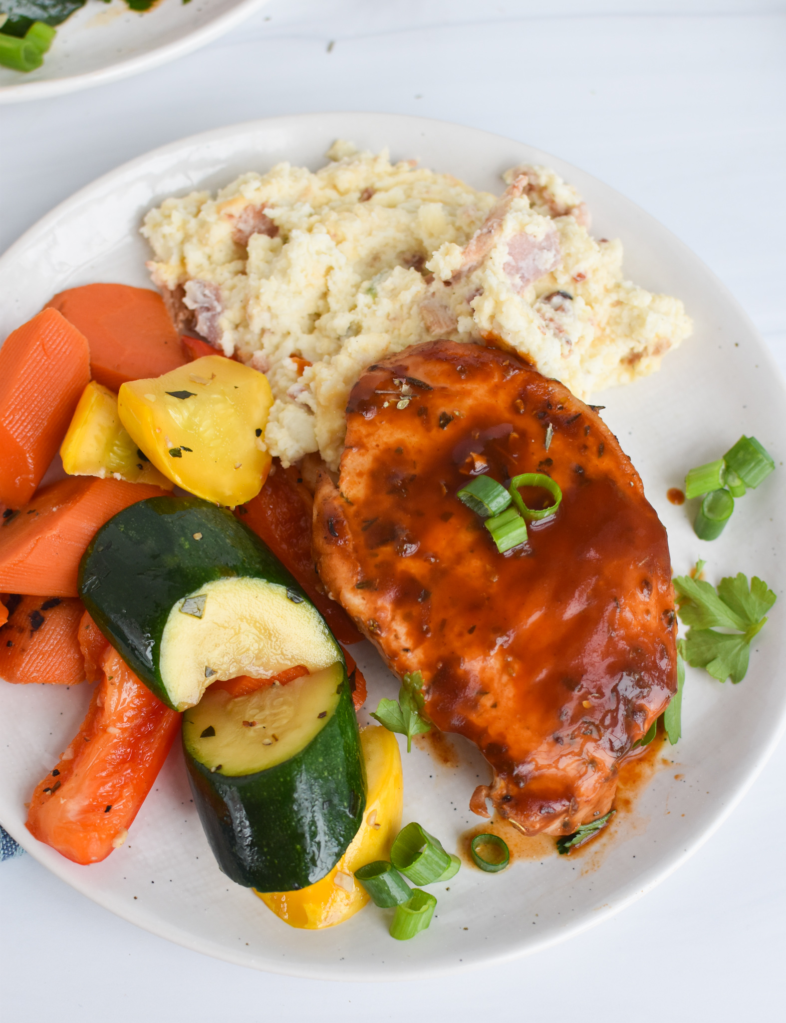 BBQ Baked Pork Chops with vegetables and mashed potatoes.