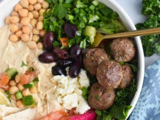 Lamb Kofta in hummus bowl with fork.