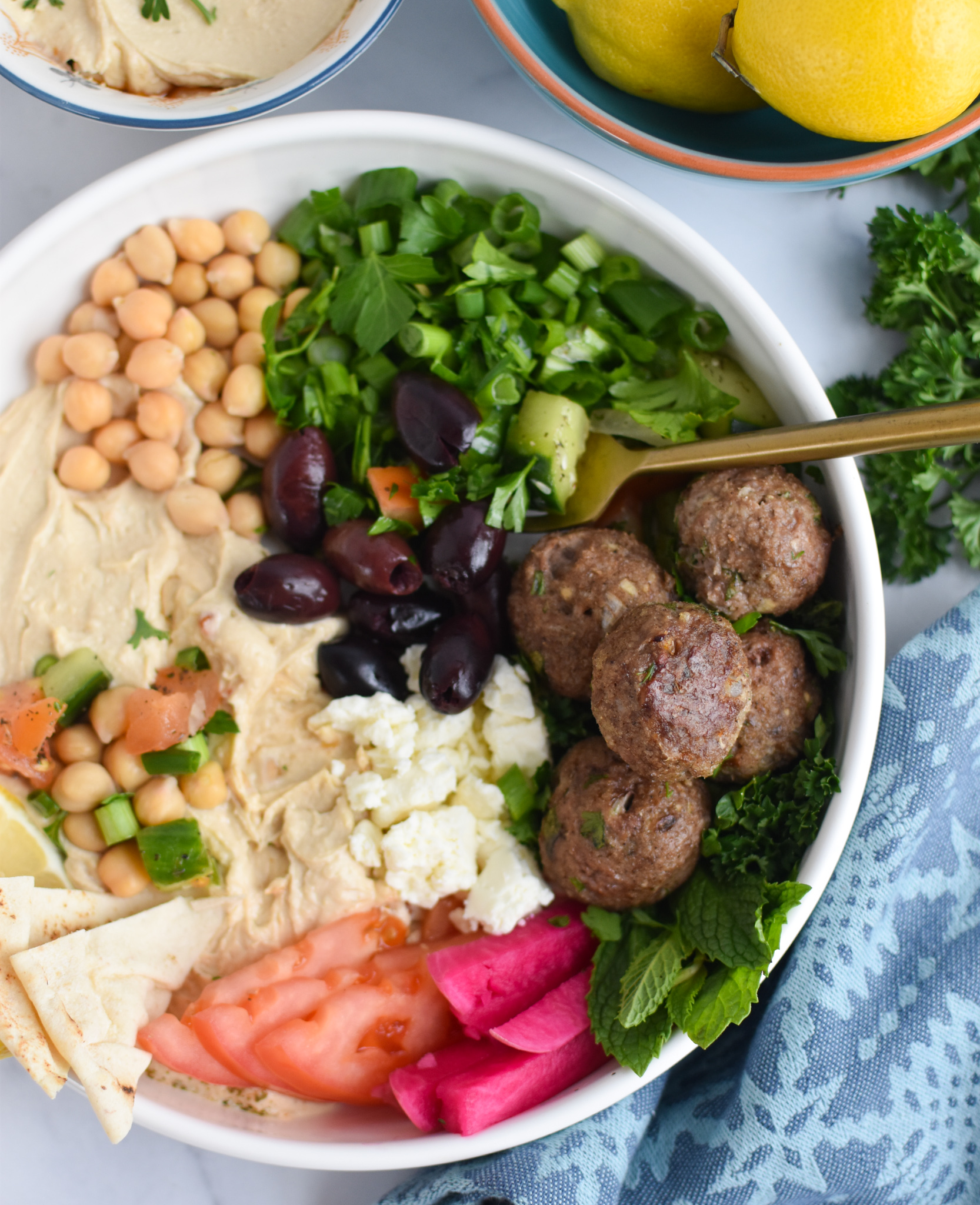 Lamb Kofta in hummus bowl with fork.