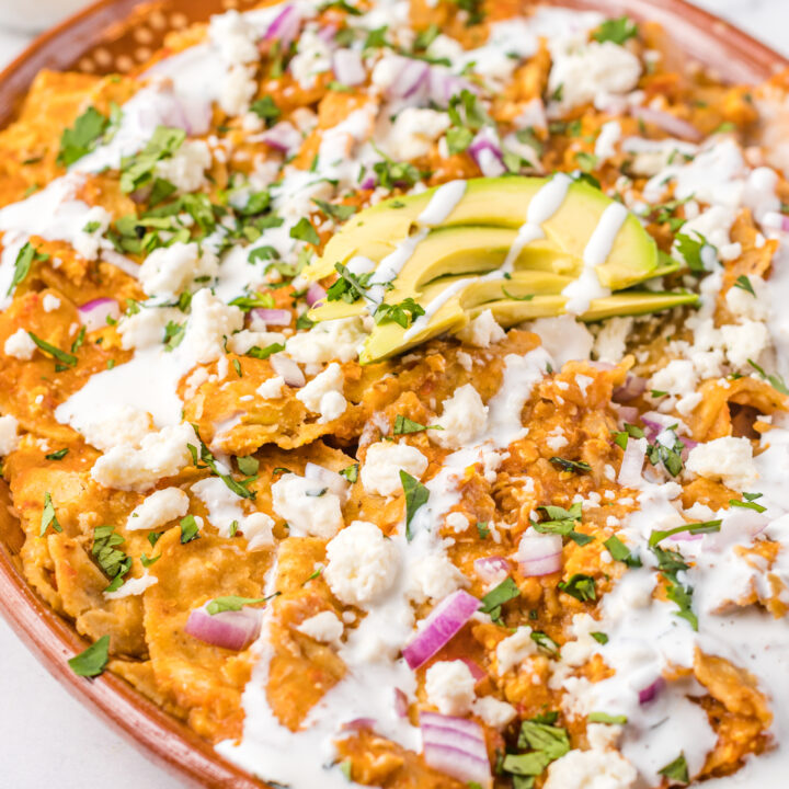 Chilaquiles Rojos Recipe on a platter with avocado on top.