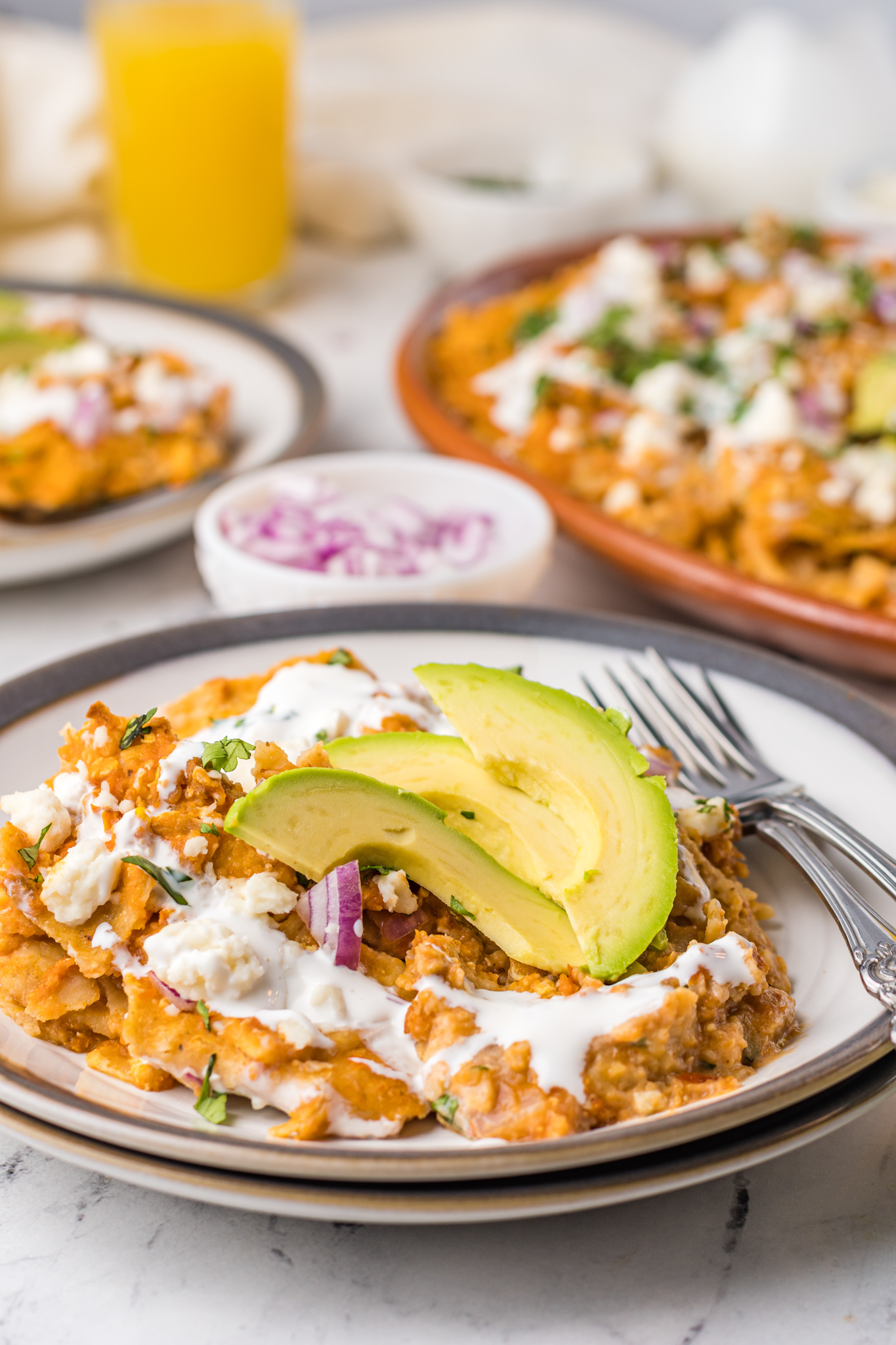 Chilaquiles Rojos Recipe on a plate with avocado.