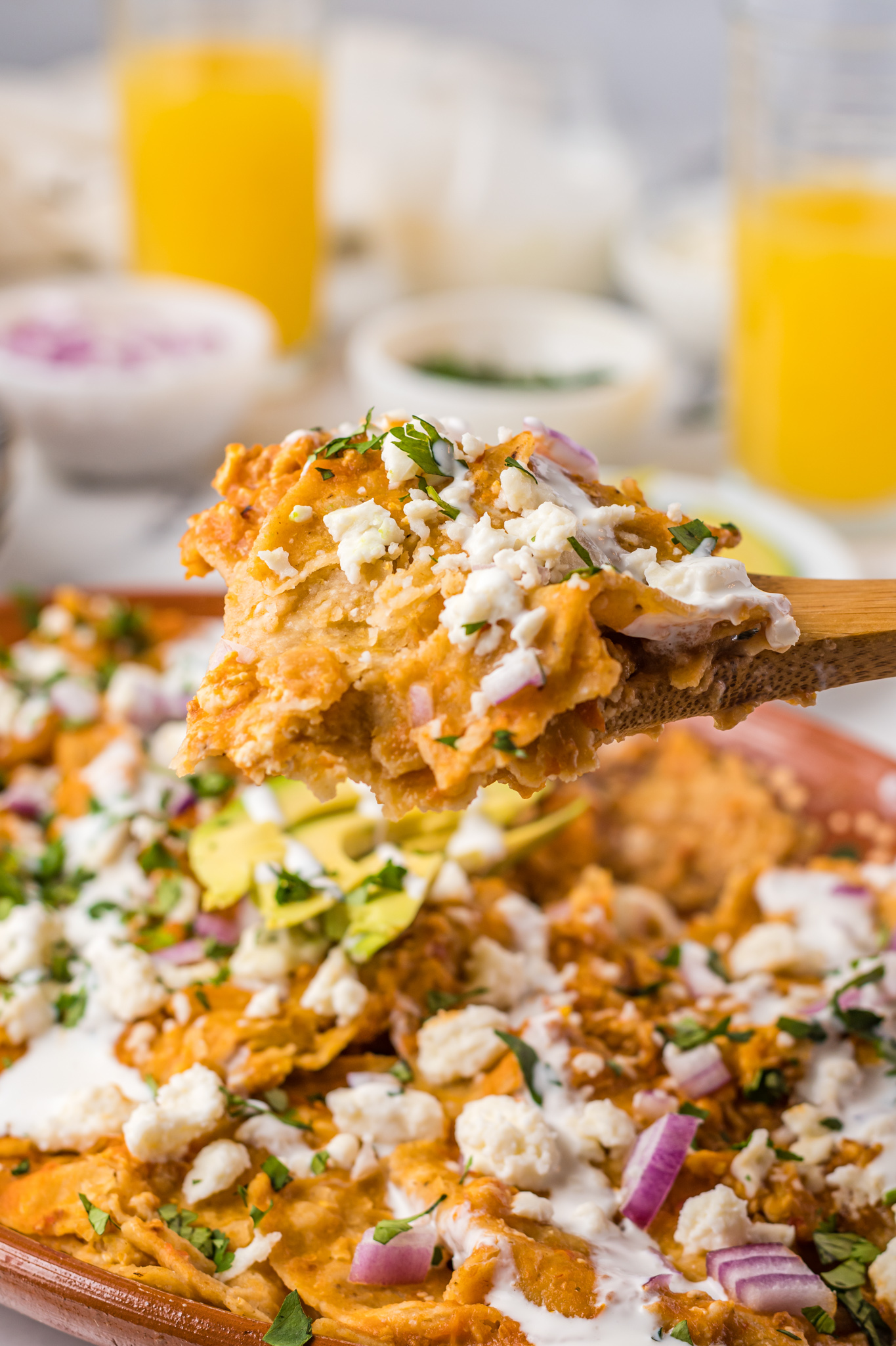 Chilaquiles Rojos Recipe with a wooden spoon holding the chilaquiles.