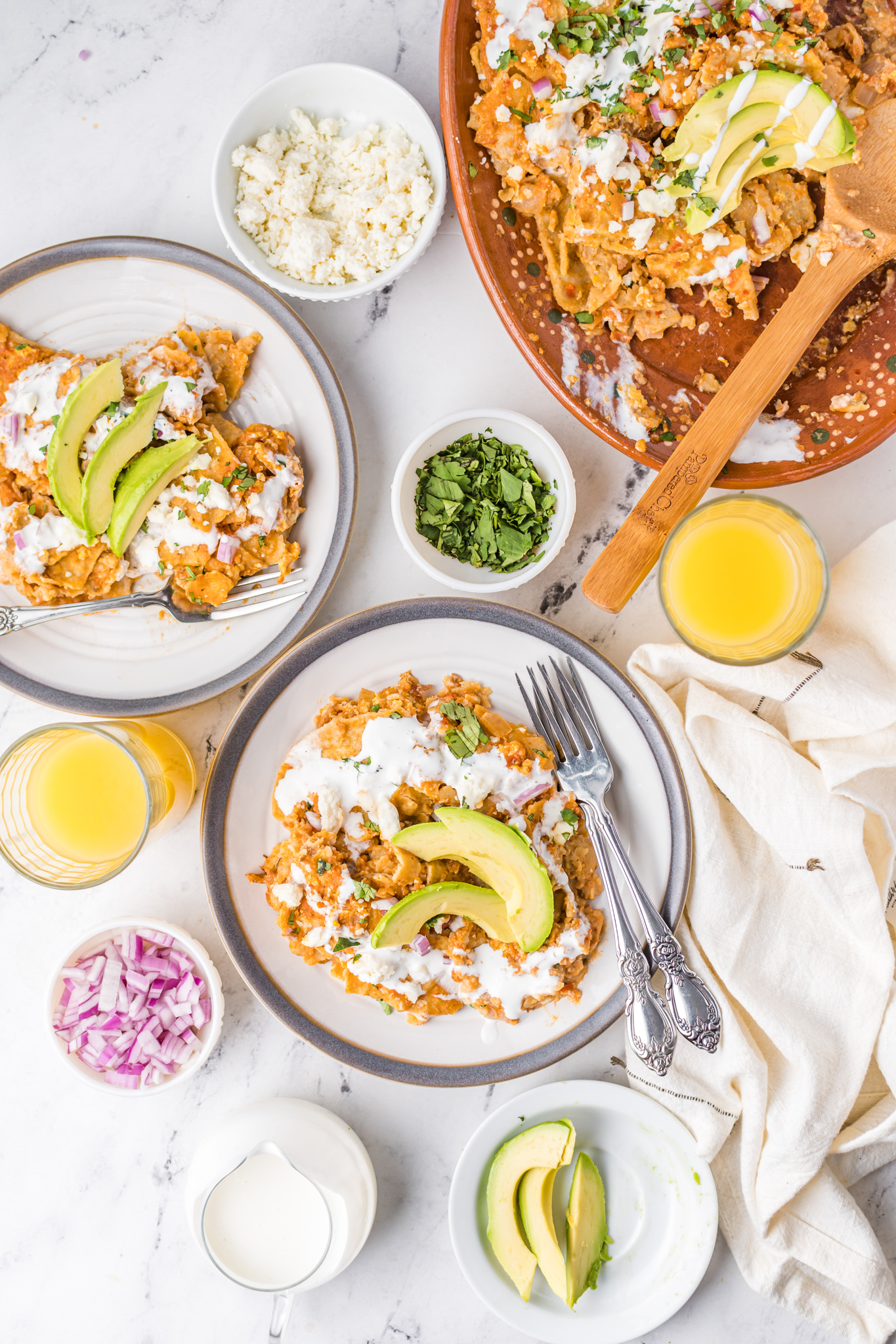 Chilaquiles Rojos Recipe with orange juice and avocado on top.