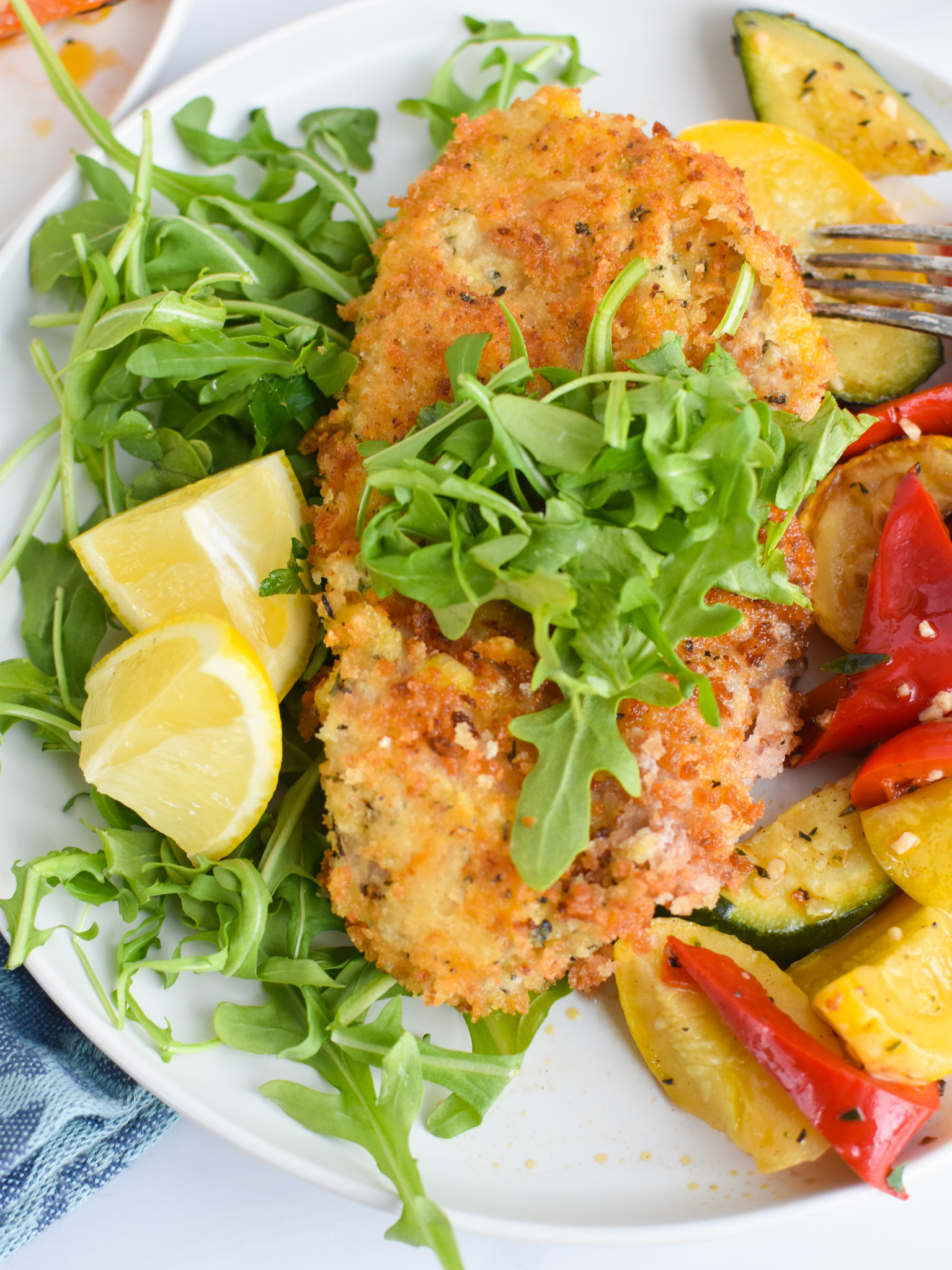 Easy Veal Milanese Recipe with lemon wedges.