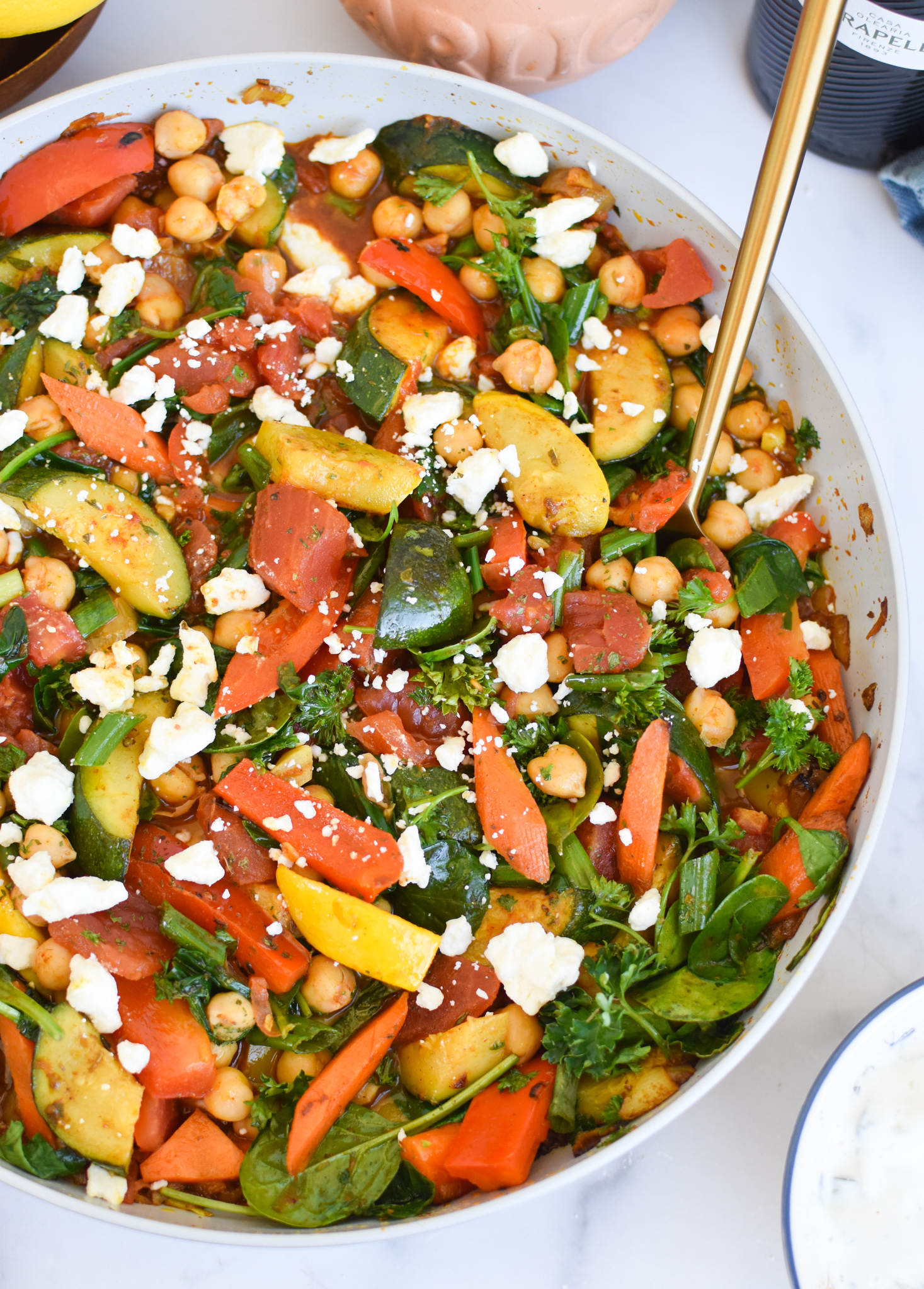 Mediterranean Chickpea Skillet with gold spoon.