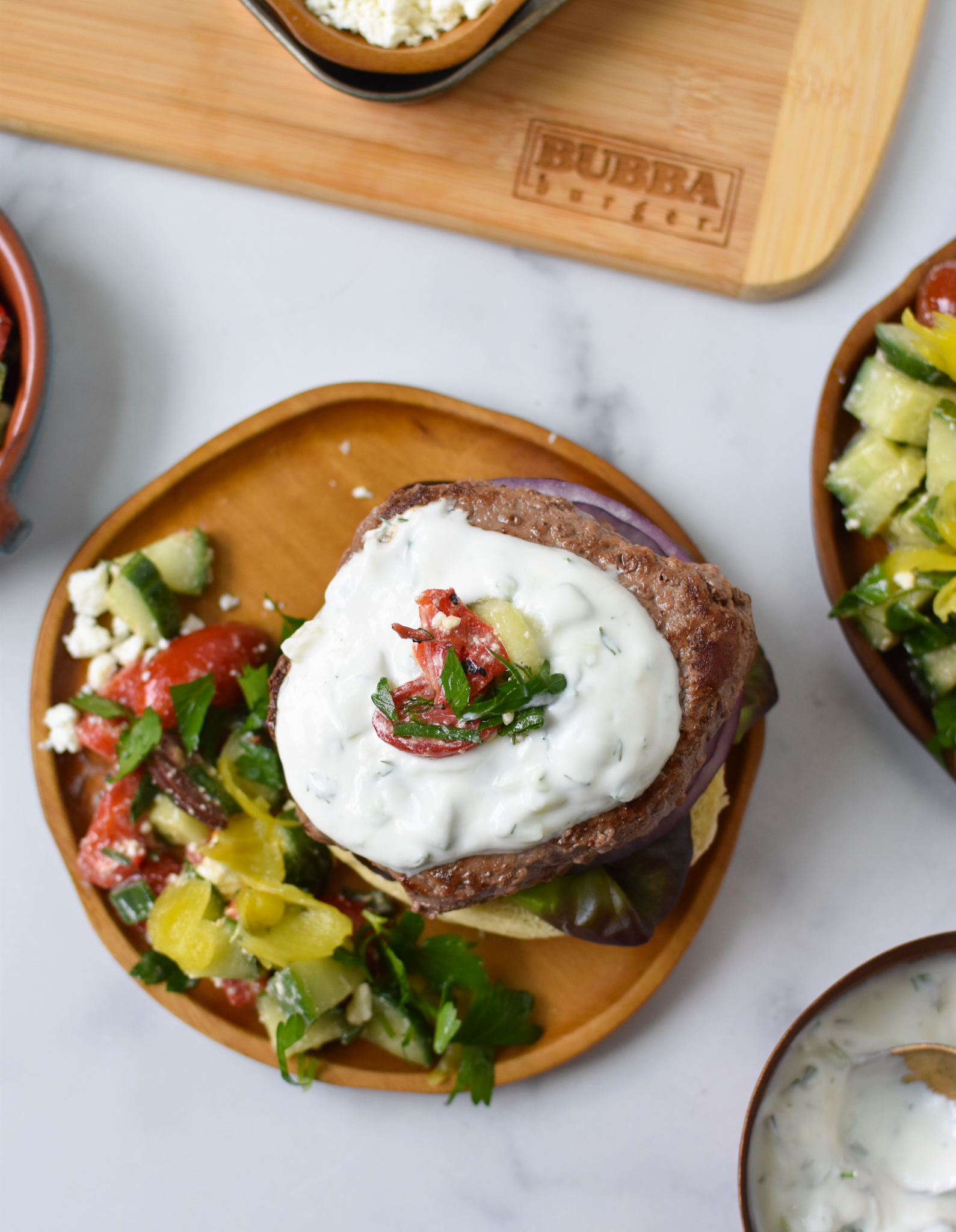 Easy Greek Burger Recipe above on wood plate.