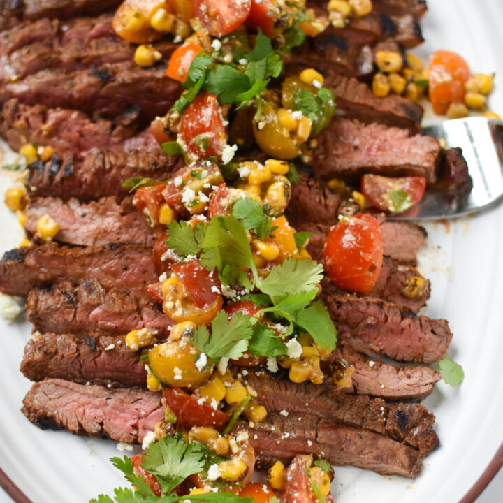 Grilled Flank Steak with Dry Rub on white platter.