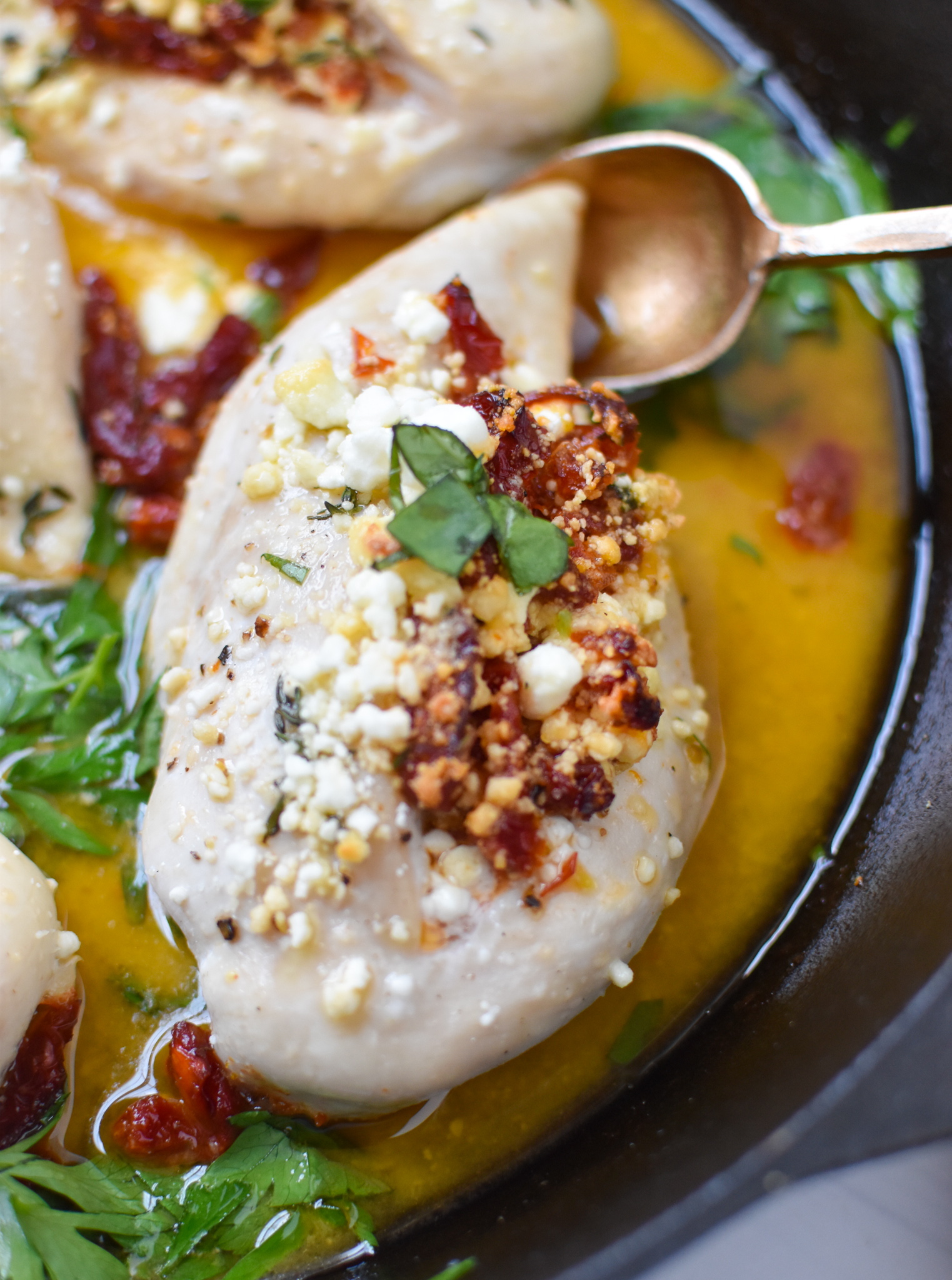 Sun-dried Tomato Goat Cheese Stuffed Chicken Breasts with spoon.