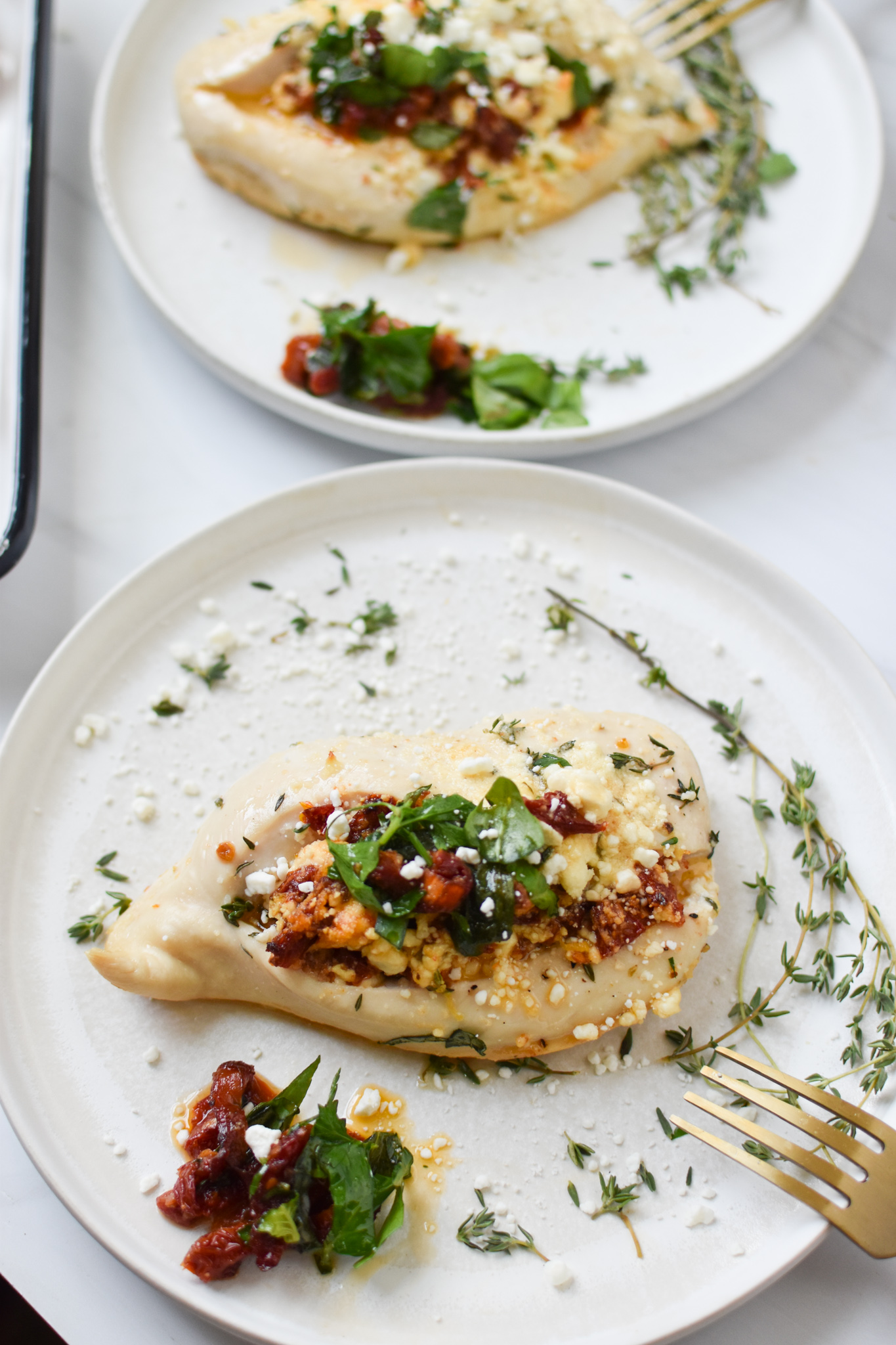Sun-dried Tomato Goat Cheese Stuffed Chicken Breasts on white plate.