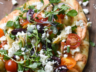 Mediterranean Naan Bread Pizza on a cutting board.