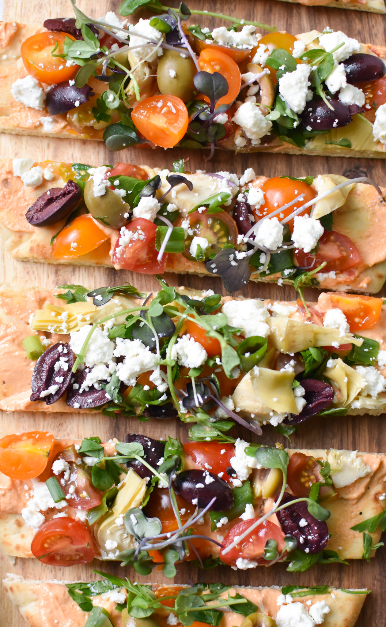 Mediterranean Naan Bread Pizza sliced on a plate.