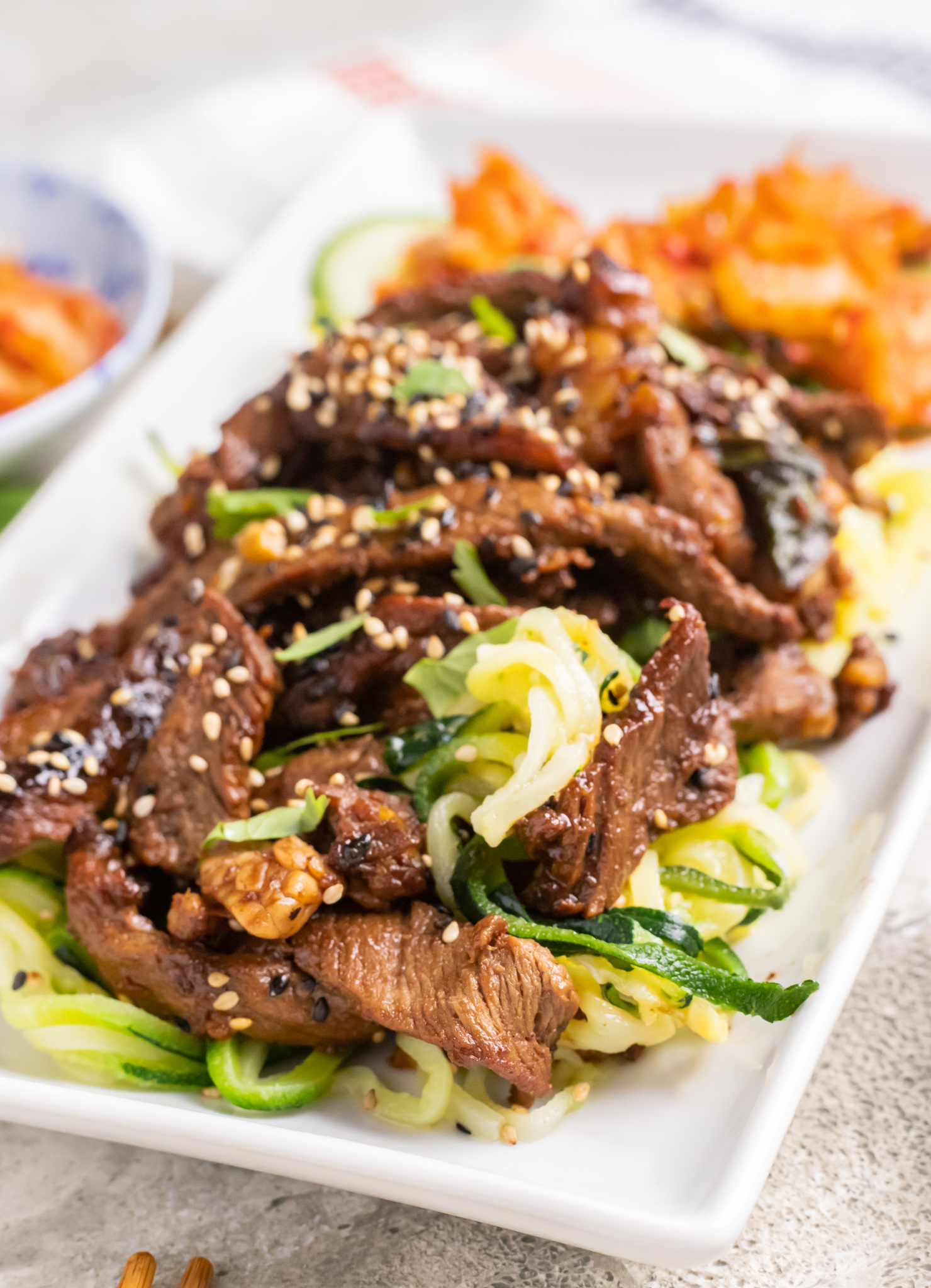 Beef Bulgogi with Zucchini Noodles on a white plate.