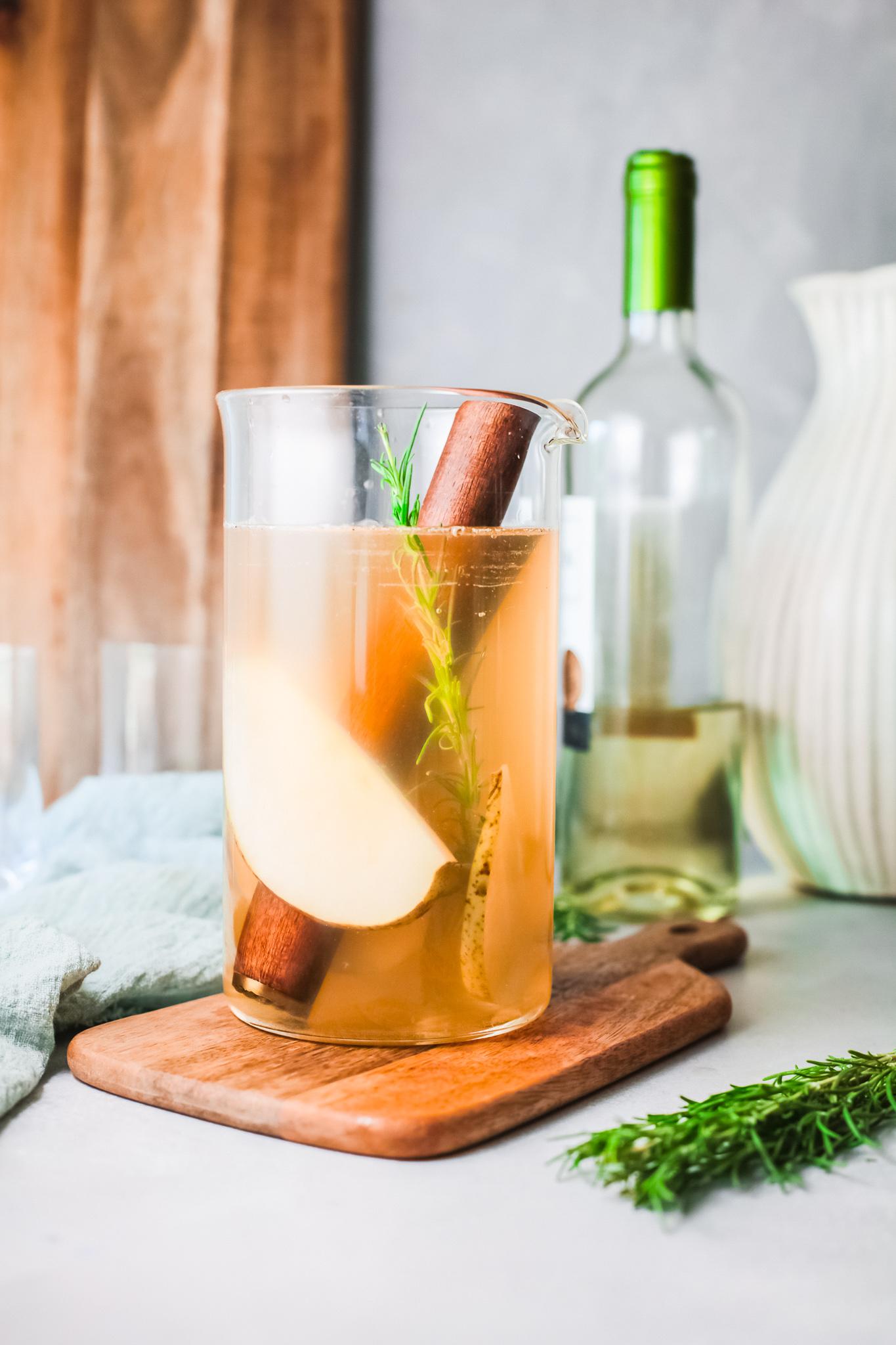 White Sangria Recipe pouring wine into pitcher.