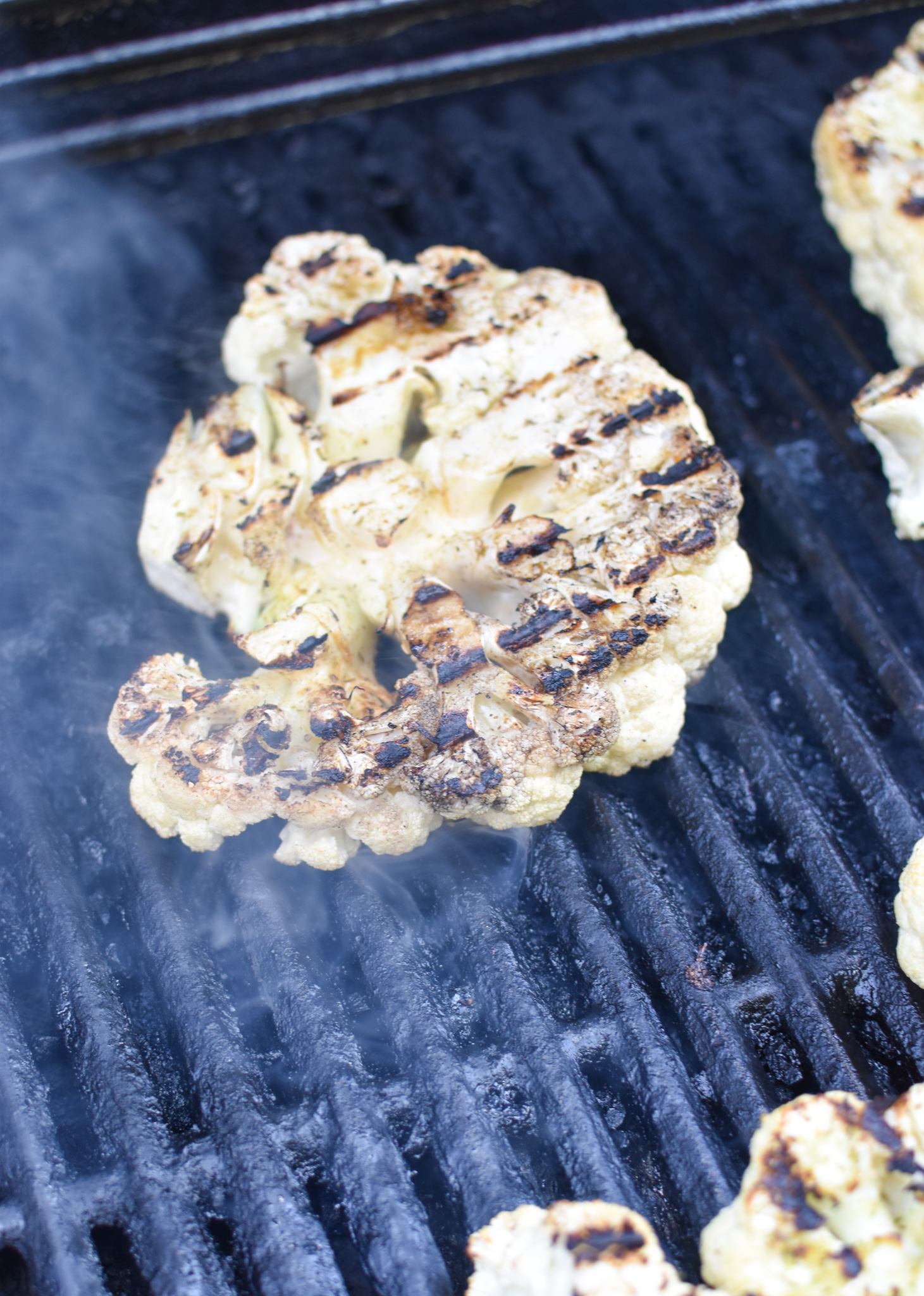 Grilled Cauliflower Steaks with Yogurt Tahini Sauce on grill.