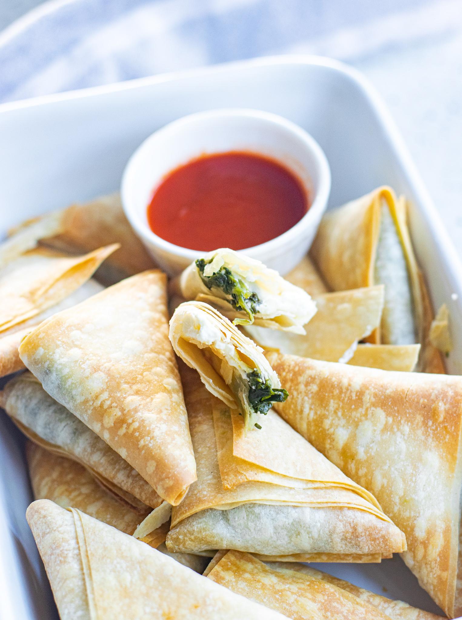 Spanakopita Triangles Recipe in white dish.