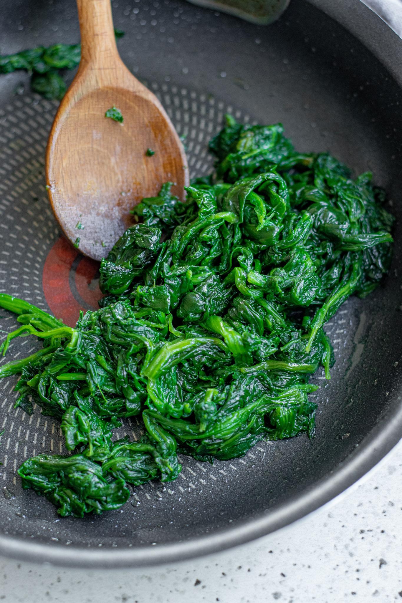 Spanakopita Triangles Recipe spinach in a pan.