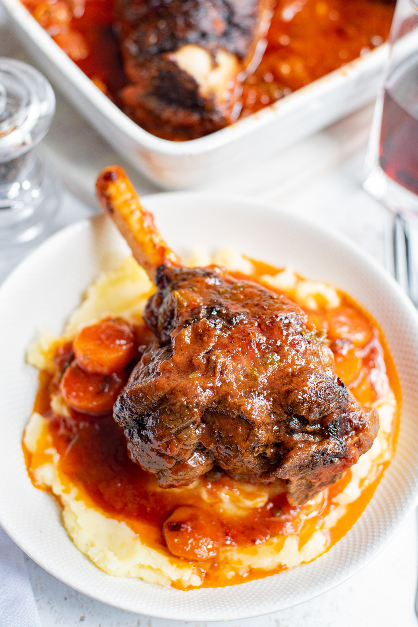 Braised Lamb Shank Recipe in a white bowl.